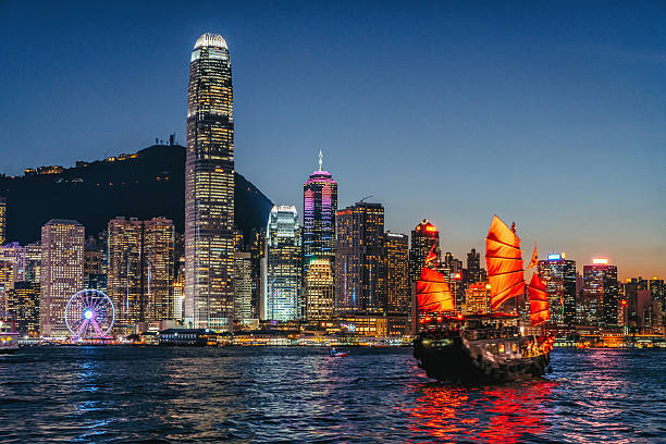 cityscape hong kong and junkboat at twilight - lugar de interés fotografías e imágenes de stock