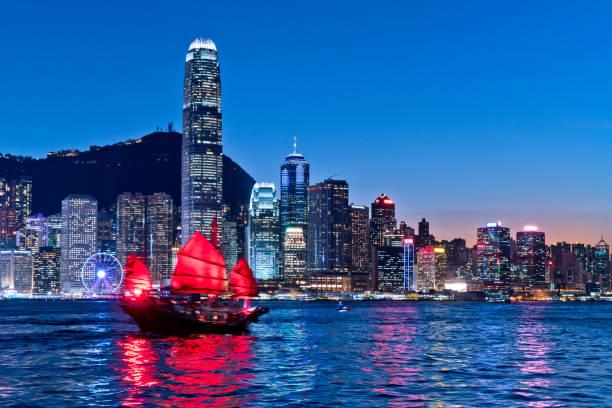paisaje urbano de hong kong y junkboat en el crepúsculo - hong kong fotografías e imágenes de stock