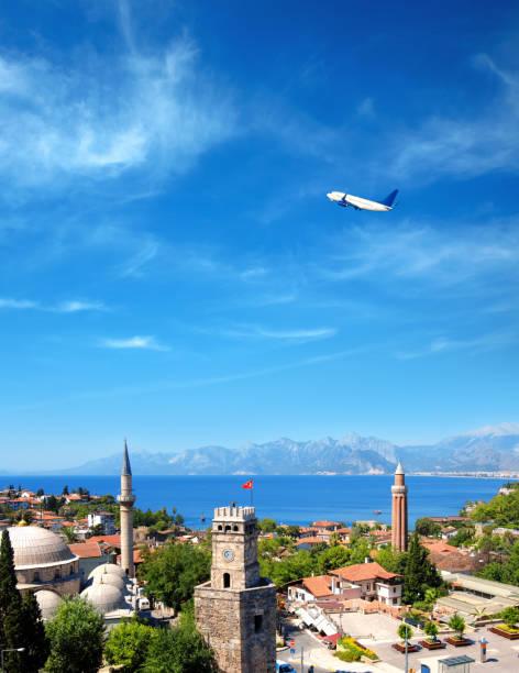 stadsbeeld van het historische district van antalya en vliegend vliegtuig over de middellandse zee en hoge bergen - minaret stockfoto's en -beelden