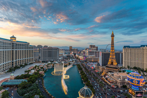 Sunset time high-angle view of the Las Vegas strip featuring the Eiffel tower replica and the fountains of Bellagio as well as the resort hotels Bellagio, Paris-Las Vegas, Ballys and Caesars Palace.