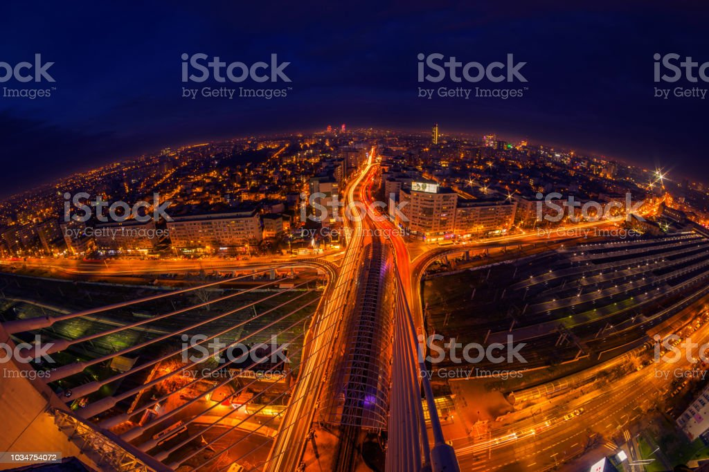 Cityscape long exposure with traffic lights and cars with modern buildings shot with fish eye lens stock photo