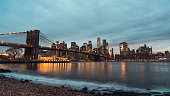 Cityscape night view of Brooklyn bridge and buildings in Manhattan New York City, United States. NYC business district, East America's landmark, USA tourist attraction, or travel destination concept