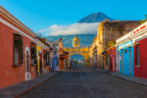 Cityscape of the main street and yellow Santa Catalina arch in the historic city center of Antigua at sunrise with the Agua volcano, Guatemala.