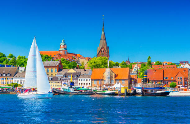 Cityscape of Flensburg. Panorama of a small European town in Northern Germany. A sailboat is floating in a harbour along the coastline with old architecture, ships and landmarks on the background stock photo