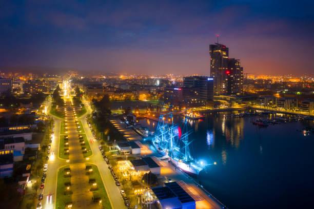 cityscape of gdynia by the baltic sea at dusk - drone shipyard night imagens e fotografias de stock