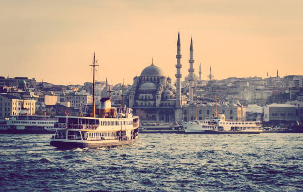 Cityscape of Istanbul with vapur. Cityscape of Istanbul at sunset - old mosque and turkish steamboats, view on Golden Horn. Muslim architecture and water transport in Turkey - touristic landmarks from sea voyage on Bosphorus. bosphorus stock pictures, royalty-free photos & images