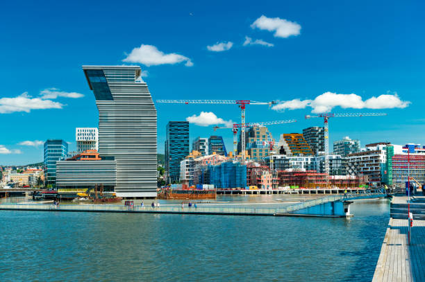 Cityscape of Oslo with modern architecture, buildings under construction, tower cranes, harbor and bridge with walking people, Norway stock photo
