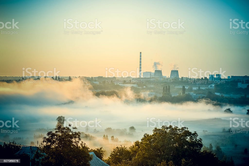 cityscape of power plants and the field with fog stock photo