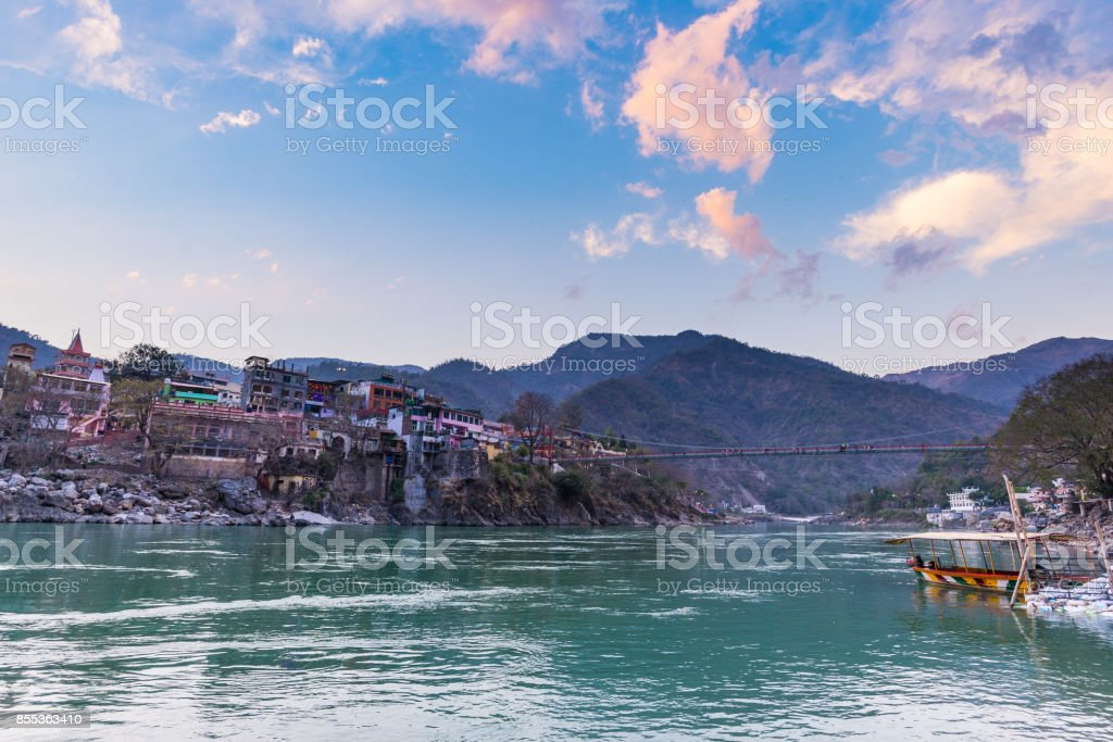 Cityscape of Rishikesh at sunset, holy town and travel destination in India. Colorful sky and clouds reflecting over the Ganges River. stock photo
