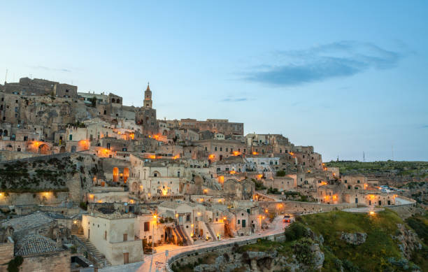 Cityscape of Sassi di Matera at dusk, Basilicata Italy Matera old town at dusk illuminated with warm street lights. matera italy stock pictures, royalty-free photos & images