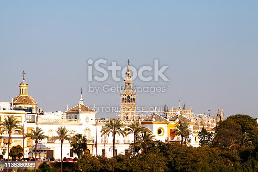 Cityscape of Seville at river seen from opposite riverside with huge tower La Giralda in background. Some people are in street in lower left area of picture.