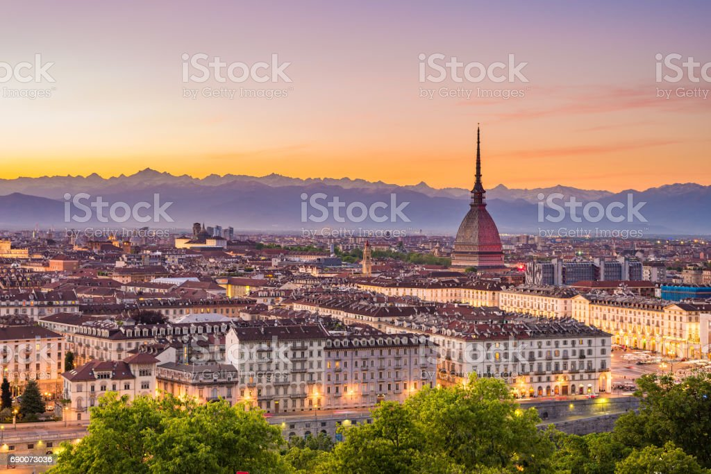 Cityscape of Torino (Turin, Italy) at dusk with colorful moody sky. The Mole Antonelliana towering on the illuminated city below. stock photo