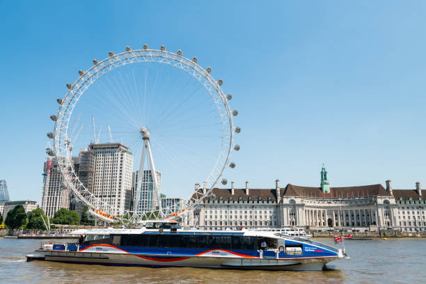Cityscape on Thames river with clippers ferry by London Eye, City Hall at Victoria Embankment stock photo