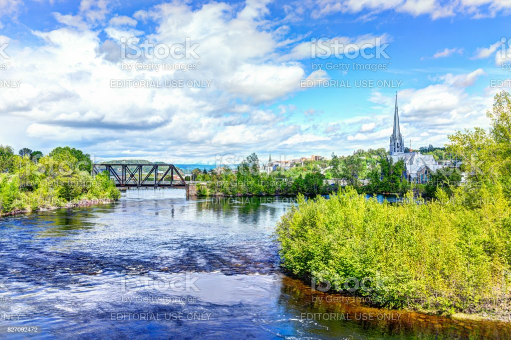 Cityscape or skyline of city in Quebec with Chicoutimi river and water flowing in summer with bridge and church stock photo