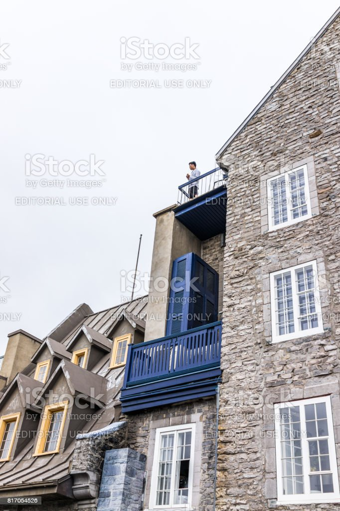 Cityscape or skyline of lower old town buildings on Rue du Petit Champlain street with person eating on balcony stock photo