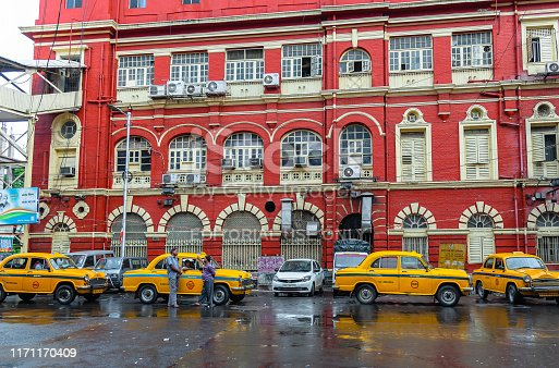 Kolkata, West Bengal/ India - August 13,2019.  Yellow Taxi parked on the Roadside Overlooking a Colonial Building.