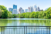 Cityscape, skyline view in Piedmont Park in Atlanta, Georgia green foliage, trees, scenic water, urban city skyscrapers downtown at Lake Clara Meer by railing