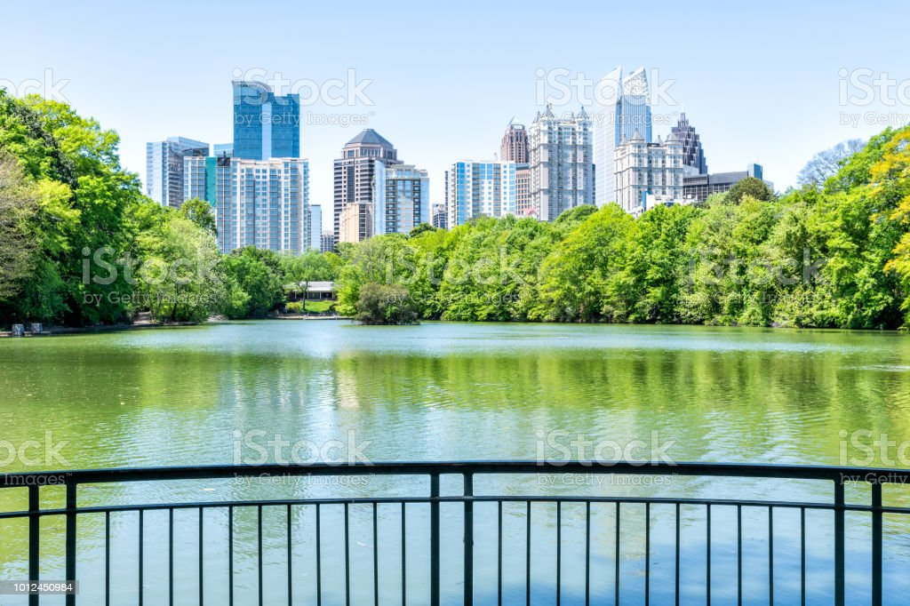 Cityscape, skyline view in Piedmont Park in Atlanta, Georgia green foliage, trees, scenic water, urban city skyscrapers downtown at Lake Clara Meer by railing stock photo