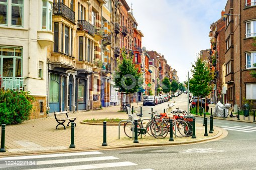 Cityscape, downtown street with typical architecture, residential district, bicycle parking, cars and benches, Brussels, Belgium
