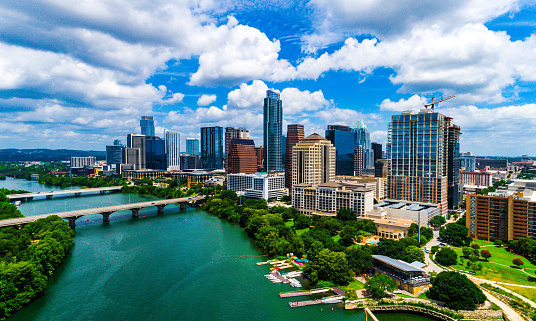 Aerial drone views with green Trees and summer landscape , bright colorful Colorado River and bridges connecting north and south Austin , Texas , USA The downtown Skyscrapers and partly cloudy skies , a beautiful sunny day in Central Texas