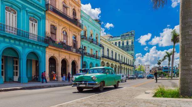 stadtbild mit amerikanischen grünen oldtimer auf der hauptstraße in havanna kuba - serie kuba reportage - urlaub in kuba stock-fotos und bilder