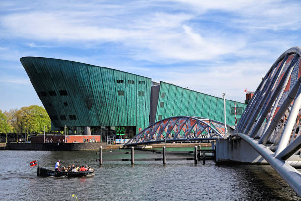 Cityscape with canal, tourists and Science Center NEMO in Amsterdam, Netherlands. Amsterdam, Netherlands - May 6, 2016: Cityscape with canal, tourists and Science Center NEMO - largest childrens science educational museum, knowledge institute and center of tourism in Amsterdam, Netherlands. nemo museum stock pictures, royalty-free photos & images