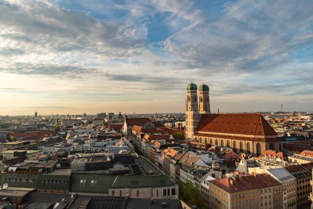 stadtbild mit der frauenkirche am sonnenuntergang - münchner frauenkirche stock-fotos und bilder