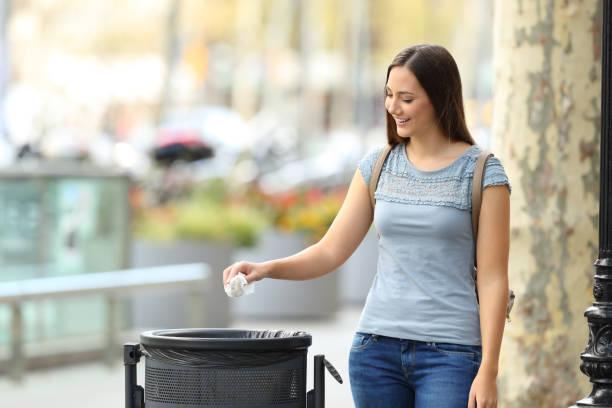 Civique femme jetant un papier dans une poubelle - Photo