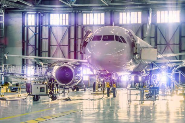 空港格納庫でのエンジンと胴体チェック修理のメンテナンスに民間飛行機ジェット。ゲートに明るい薄い紫色の濃淡。 - 航空整備士 ストックフォトと画像