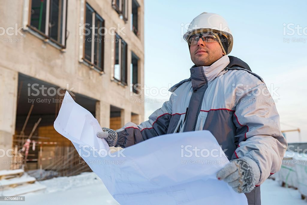 Civil Engineer At Construction Site Civil Engineer at construction site is inspecting ongoing production according to design drawings. Adult Stock Photo