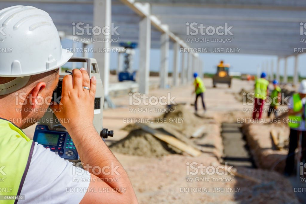 Civil engineer, geodesist is working with total station on a building site stock photo