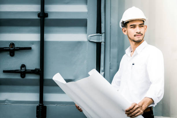 civil engineer holding blueprint at the construction site. - civil engineer stock photos and pictures