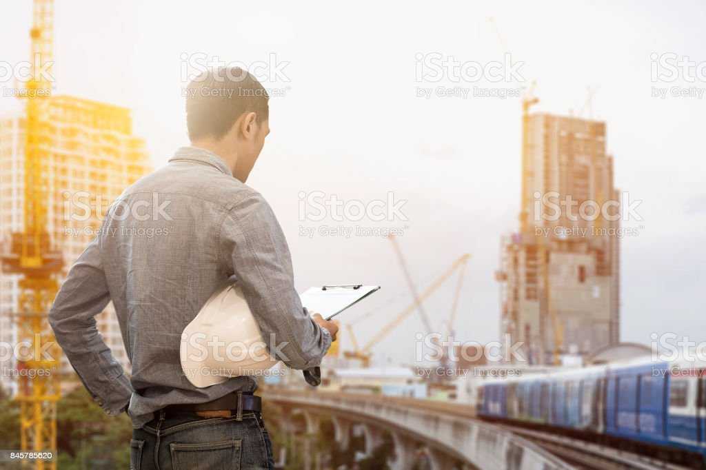 civil engineer holding helmet and working checklist construction with...
