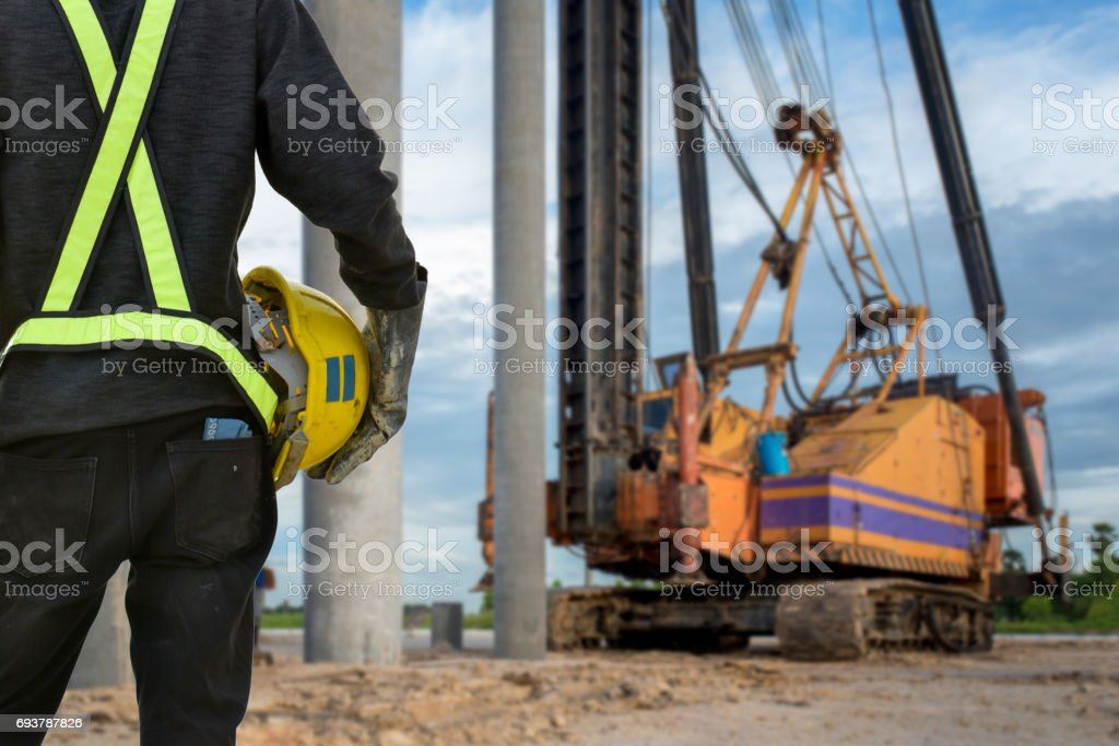 civil engineer inspection construction site concrete pile driving in safety uniform protection stock photo
