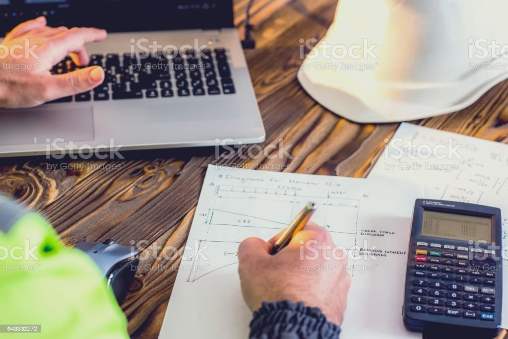 Civil Engineer making Structural Analysis Calculations Civil Design Engineer is making structural analysis calculations using a scientific calculator. Analyzing Stock Photo