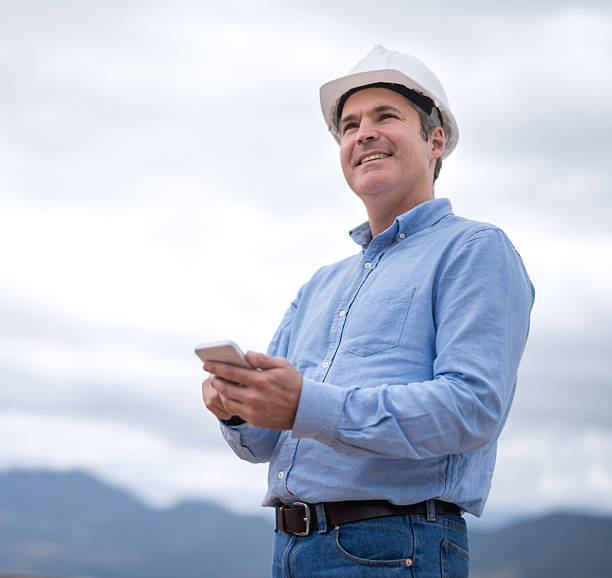 civil engineer texting on his phone - civil engineer stock photos and pictures
