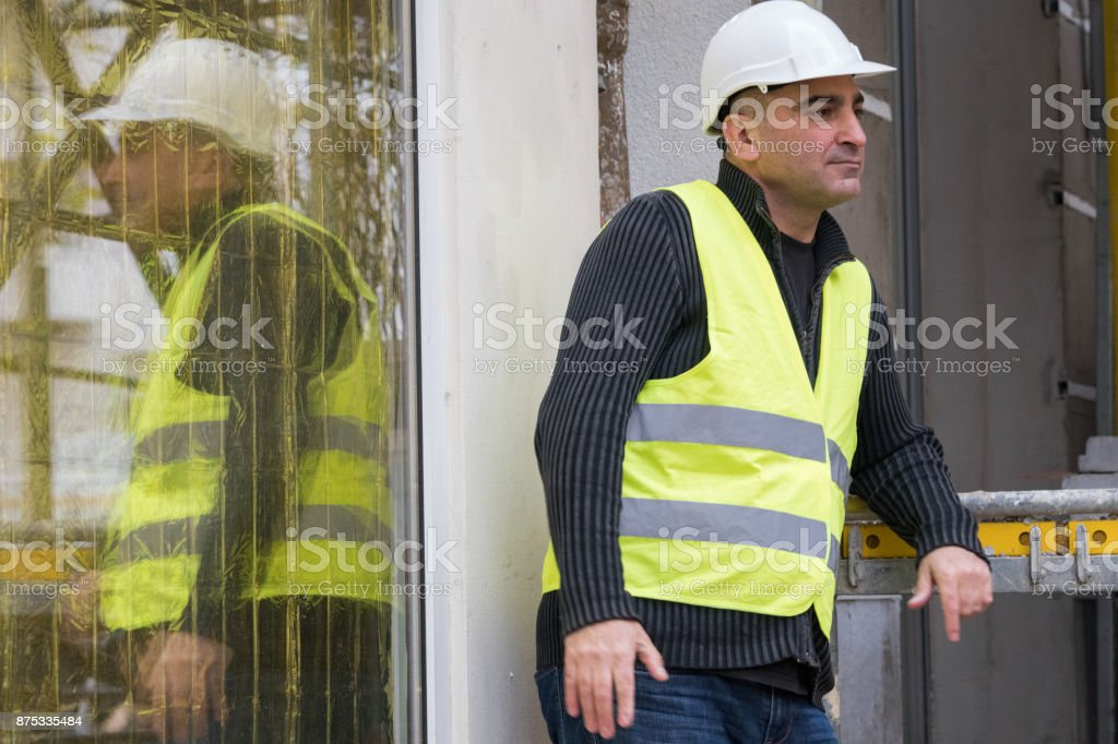 Civil engineer wearing safety protective work wear laying against...