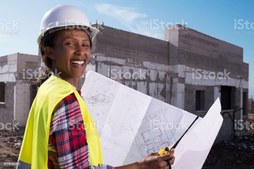 Constructor female worker looking on work plans / blueprints at a...