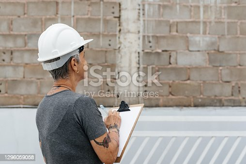 Civil engineer woman taking notes on clipboard