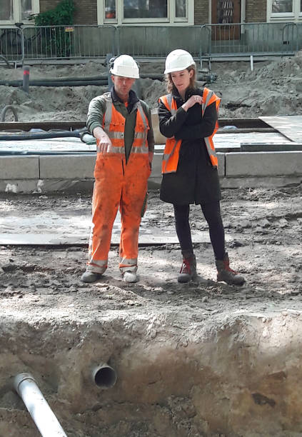 Civil engineer woman working with men at construction site. stock photo
