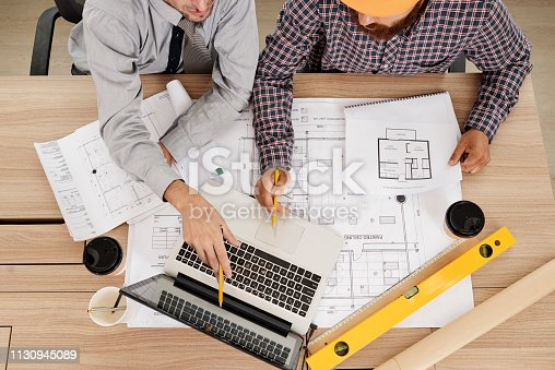 Civil engineers discussing information on laptop screen and sharing ideas, view from above