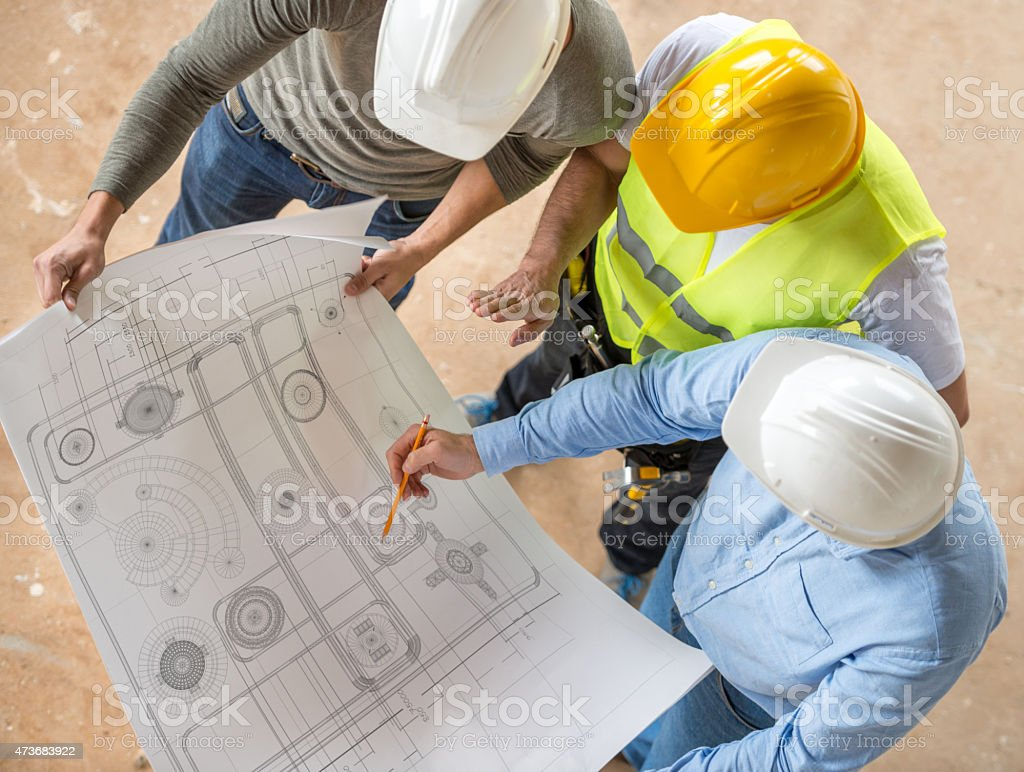 Civil engineers looking at blueprints stock photo
