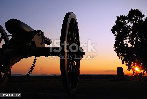 A cannon from the American Civil War sits silently at sunset at Gettysburg National Battlefield