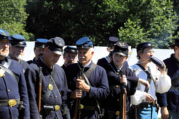 civil war Woodbury, USA - August 24, 2013: The group of men in 1800's soldier's uniform at a campsite are some of the many re-enactors impersonating individuals of the American Civil War. The individuals are taking part in the reenactment of the American Civil war saga