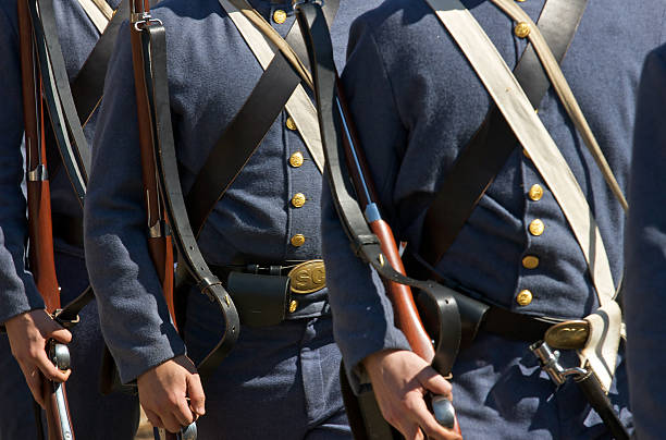 US Civil War re-enactors Civil War re-enactors march in formation carrying period (1860s) equipment and muskets. american civil war stock pictures, royalty-free photos & images