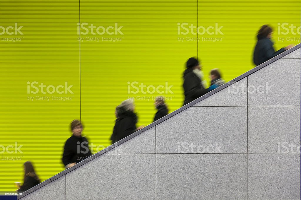 Civilians riding an escalator with a green screen background stock photo