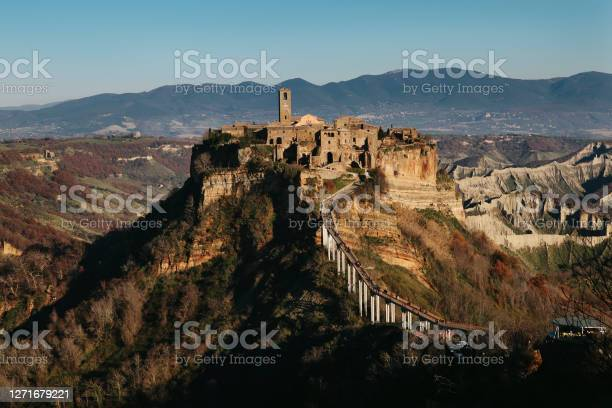 Photo of Civita di Bagnoregio - ancient hilltop village in Italy. Almost ruins, abandoned, travel destination. View from distance - with mountains panorama on winter day.
