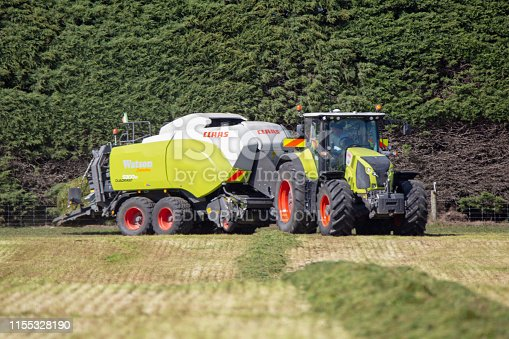 Kirwee, Canterbury, New Zealand, March 27 2019: A Claas baler and tractor at work making hay bales at the South Island Agricultural Field Days event