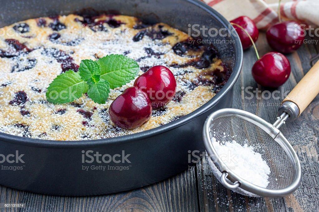 Clafoutis with cherry in baking dish, horizontal stock photo