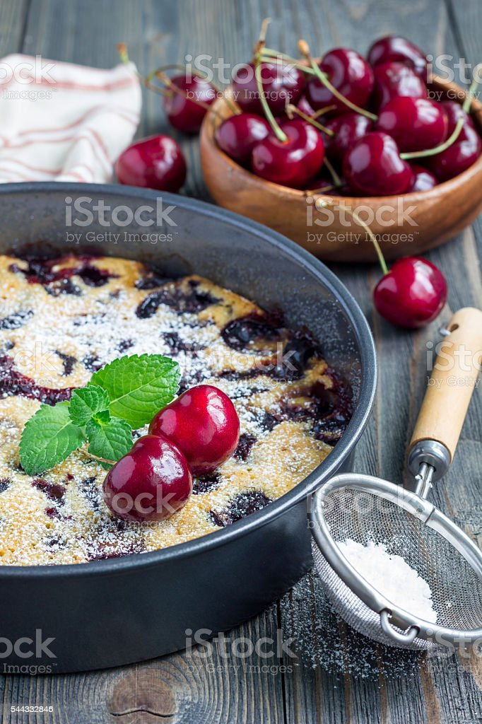 Clafoutis with cherry in baking dish, vertical stock photo